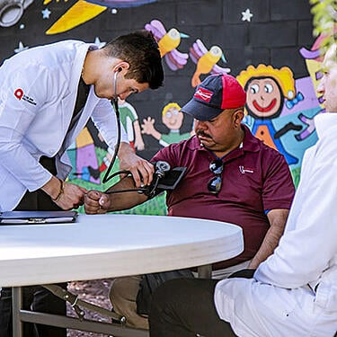 Photo of doctors examining a man - The SmartSimple's Premium Support helped improved client's skills and knowledge of the system