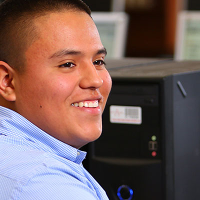 A smiling male employee at work in front of a computer