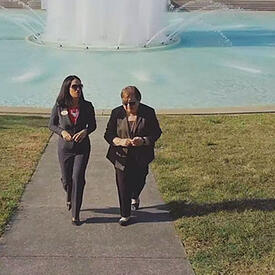 Two women walking on a pathway in front of a water fountain