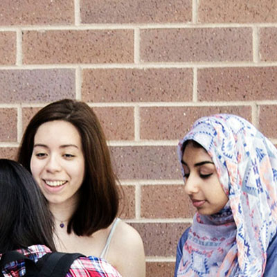 Three students conversing outside a school in front of a brick wall