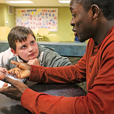 Photo of tutor with boy - New Hampshire Charitable Foundation and SmartSimple Software