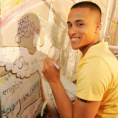 Photo of a young man painting a mural - The SmartSimple development team was highly responsive