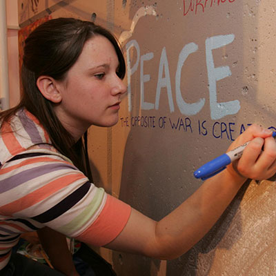 Photo of girl writing on wall - Rotary members believe in shared responsibilities