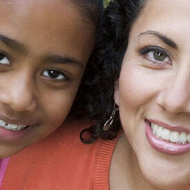 Mother and daughter, smiling, looking into the camera