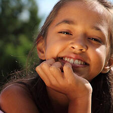 Young girl resting her chin on her hand smiling at the camera