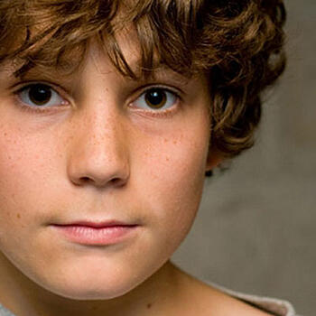 Young boy with curly hair looking at the camera