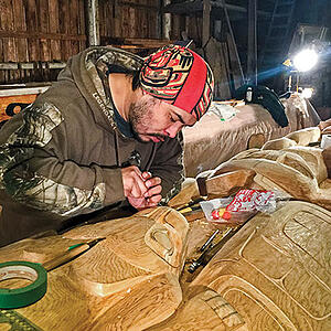 A man working on a wood-carving of a totem pole