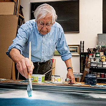 An elderly man applying a paint brush to a canvas laying on a table