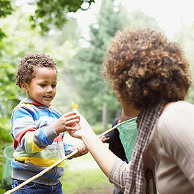 A mother is handing her young daughter a yellow flower in a park setting