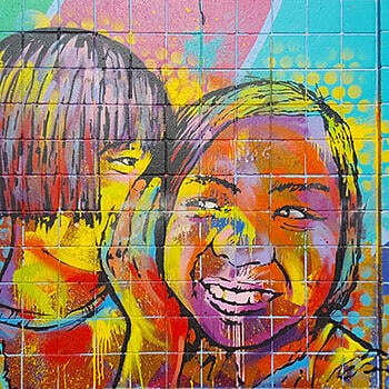 A colorful painted wall mural depicting two children sharing a private conversation