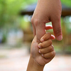 Close up photo of a father's hand holding a child's hand