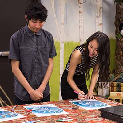 Two youths working on their artworks