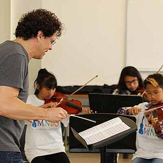 A music conductor working with children musicians