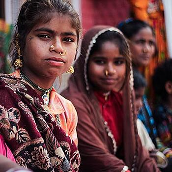 South Asian girls, in traditional wear, looking at camera