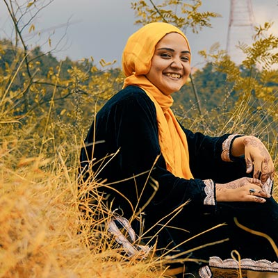 A young Muslim girl sitting on a hill side
