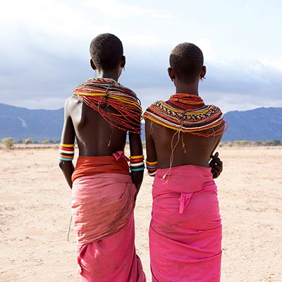 Two African girls in traditional dress looking a mountain range