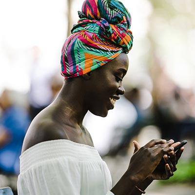 A young African woman in traditional wear is using her mobile phone