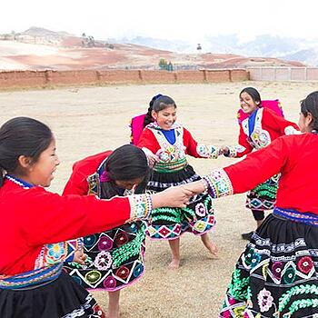 A group of South American girls, in traditional dress, playing outside