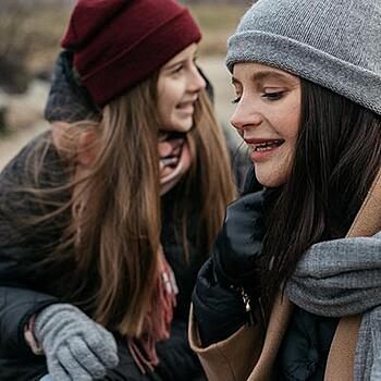 2 young women, in winter clothes, talking outside