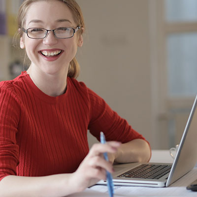 Smiling woman grantmaker working virtually from home