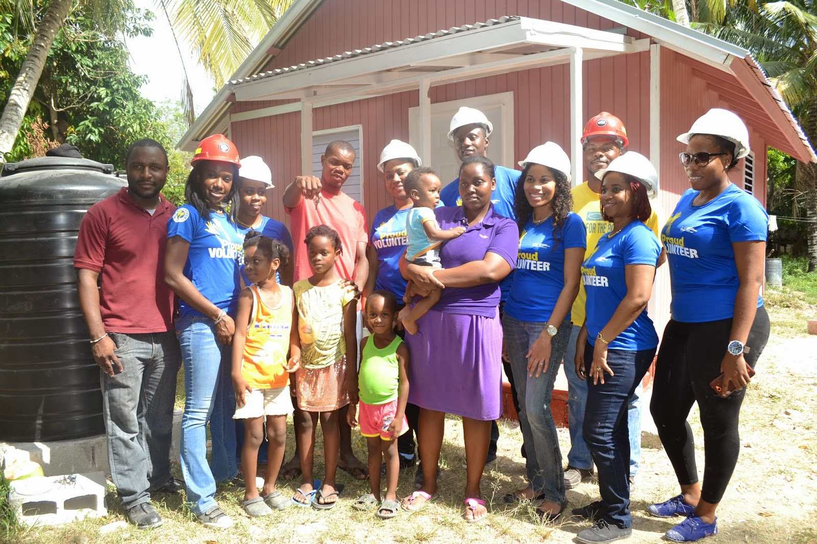 Volunteers from the National Commercial Bank Foundation and Food For The Poor Jamaica, standing before the new house that was constructed for a family in need.