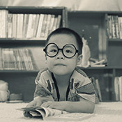 A photo of a little boy with round rimmed glasses at the library