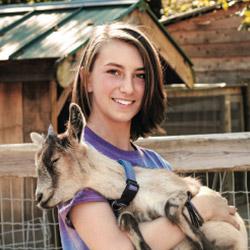 A smiling girl holding a baby goat in front of a farm