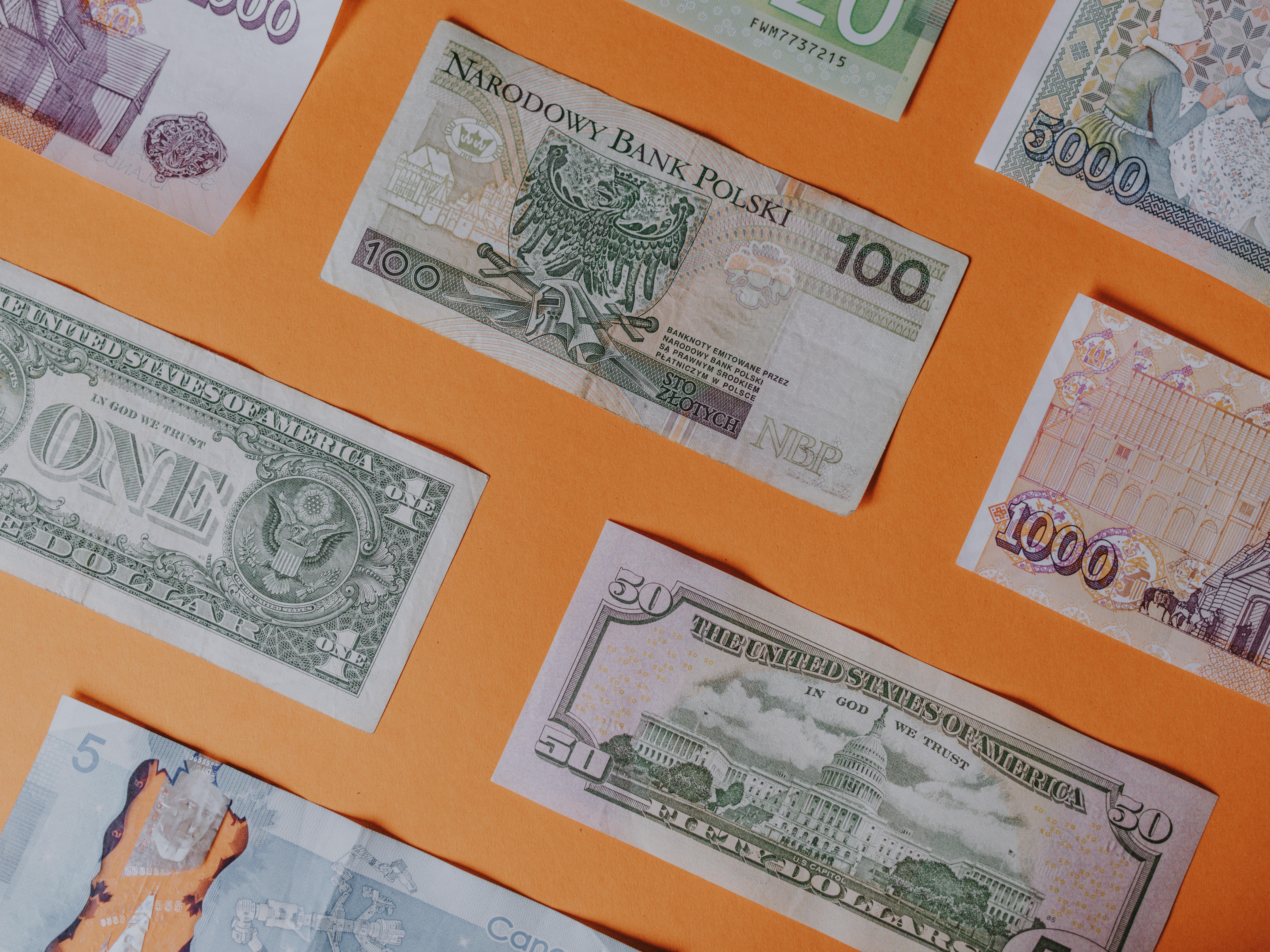 Photo of money from around the world with orange background